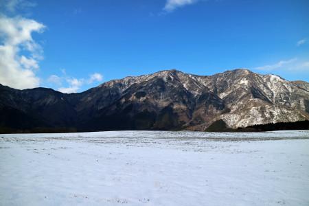 雪の朝霧高原牧草地と毛無の山々